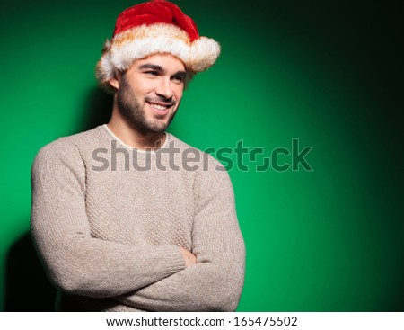 smiling young santa man standing relaxed and looking away on green background - stock photo