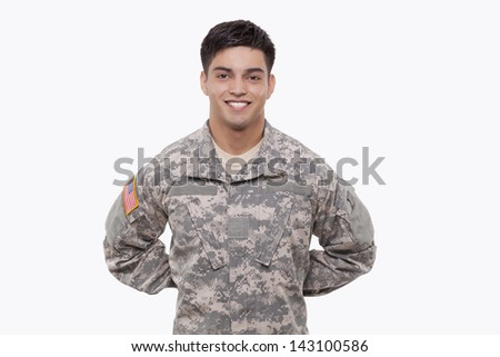 Smiling young soldier with hands behind back  - stock photo