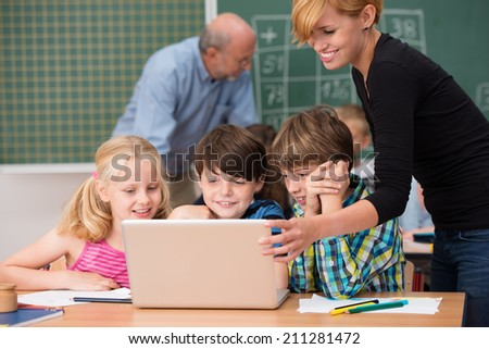 Smiling young teaching assistant helping a young girl and two boys seated in front of a laptop computer with an elderly male teacher working in the background - stock photo