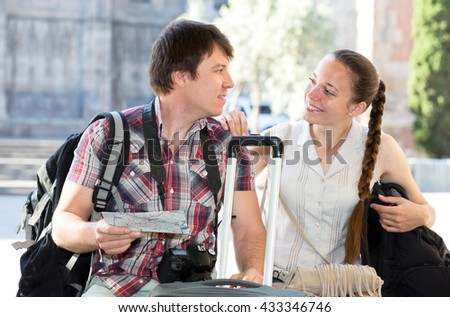 Smiling young tourist couple looking at the map in the city - stock photo