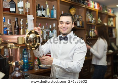Smiling young waitress and barmen working in modern bar - stock photo