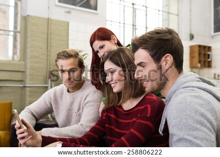 Smiling Young White Friends Watching Something at Mobile Phone While Resting at the Living Room. - stock photo