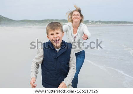 Smiling young woman and cheerful boy running at the beach - stock photo