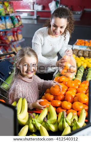Smiling young woman and little girl purchasing sweet tangerines at market