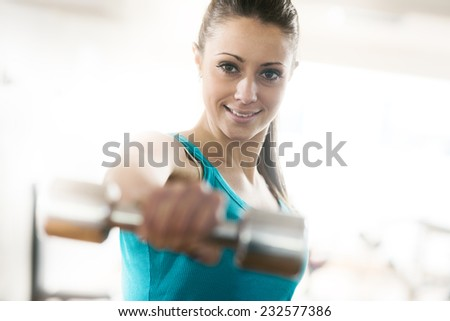 Smiling young woman at gym working out with dumbbells. - stock photo
