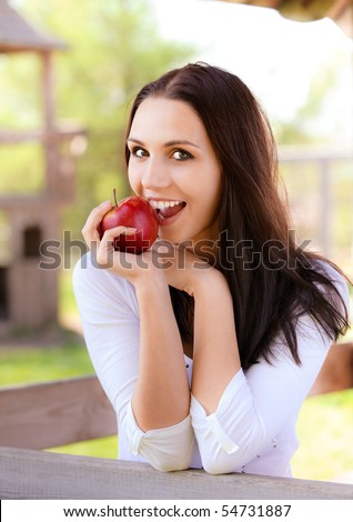 Smiling young woman bites red apple - stock photo