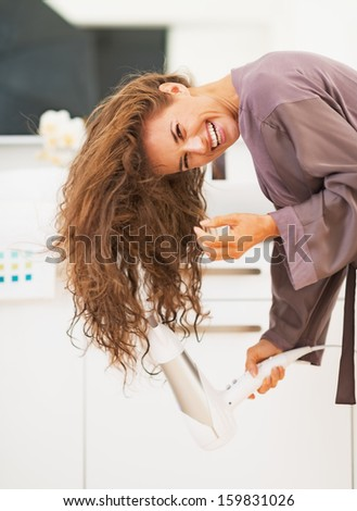 Smiling young woman blow drying hair in bathroom - stock photo