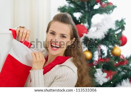 Smiling young woman checking Christmas socks - stock photo