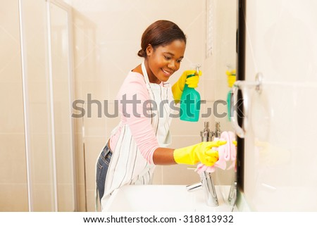 smiling young woman cleaning bathroom mirror at home