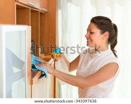 Smiling young woman cleaning furniture at home with atomizer and rag