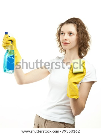 Smiling young woman cleaning something using sponge and sprayer; white background - stock photo
