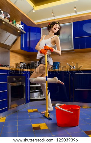 Smiling young woman cleaning the floor at home and singing - stock photo