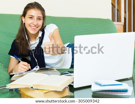 Smiling young woman college student study in living room - stock photo