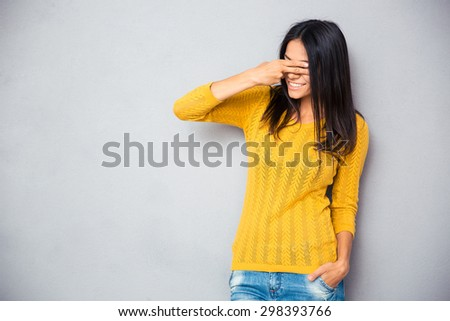 Smiling young woman covering her eyes with fingers over gray background - stock photo