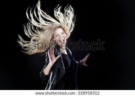 smiling young woman dancing, on a black background - stock photo