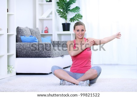 Smiling young woman doing stretching exercise at her home. - stock photo