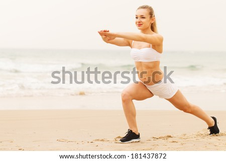Smiling young woman doing stretching exercise at the beach. - stock photo