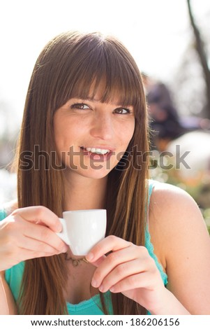 Smiling young woman drinking espresso in turquoise tank top