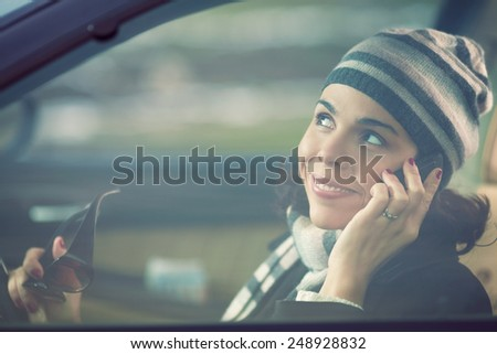 Smiling young woman driving a car and talking on the mobile phone - stock photo