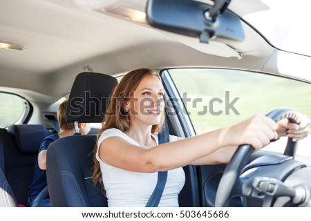 Smiling young woman driving a car at summer day with her son on the back seat