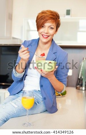 Smiling young woman eating fresh fruits in modern kitchen
