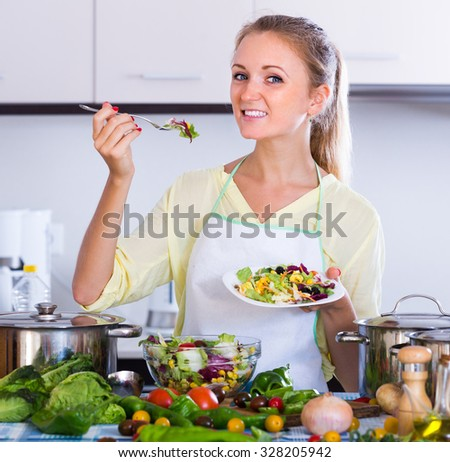 Smiling young woman eating healthy salad with corn, cabbage and carrot at kitchen
