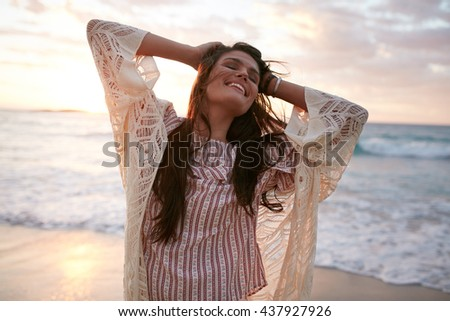 Smiling young woman enjoying her summer vacation on the beach. Beautiful female model having fun on the sea shore. - stock photo