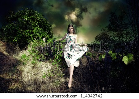 smiling young woman fairy like in elegant dress in dark green environment - stock photo