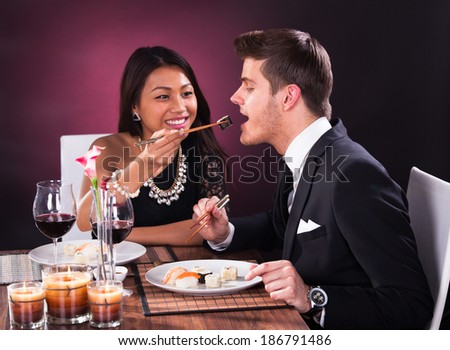 Smiling young woman feeding man at restaurant table - stock photo