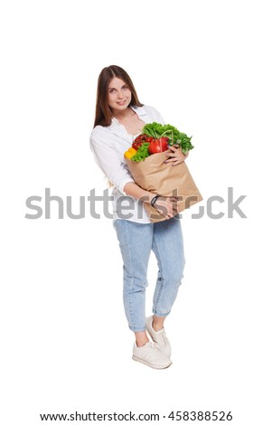 Smiling young woman full length portrait, holding shopping bag full of groceries isolated at white background. Healthy food shopping. Paper package with vegetables and fruits, happy female buyer
