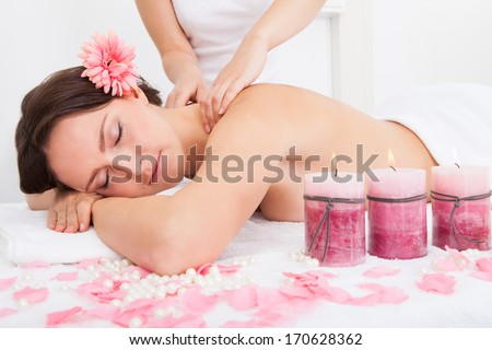 Smiling Young Woman Getting Massage Treatment From Masseuse - stock photo