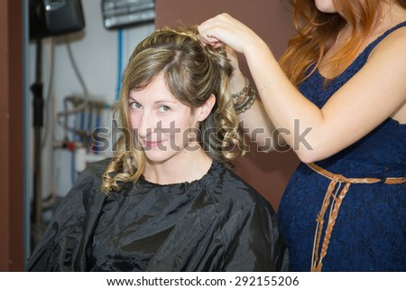 Smiling Young woman hairdo at hairdressing salon doing a bun