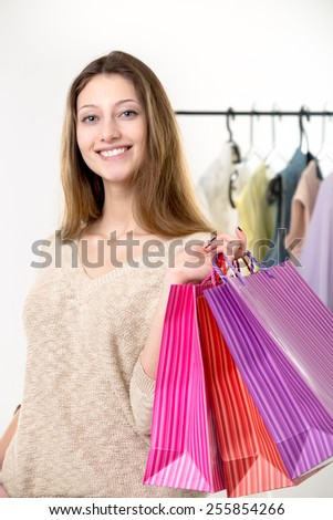 Smiling young woman happy after buying goods, shopping, carrying colorful paper bags - stock photo