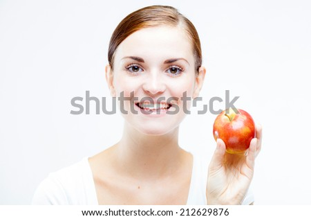 Smiling young woman holding and eating red apple, Healthy teeth concept