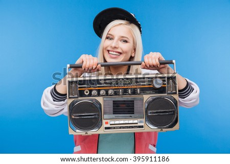 Smiling young woman holding boom box over blue background - stock photo