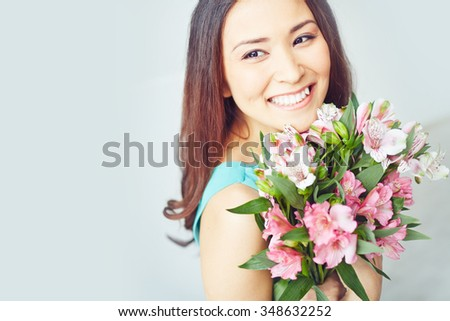 Smiling young woman holding floral bouquet - stock photo