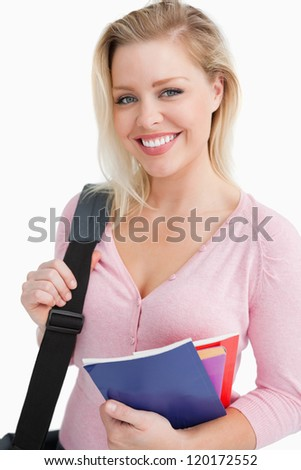 Smiling young woman holding school books against a white background