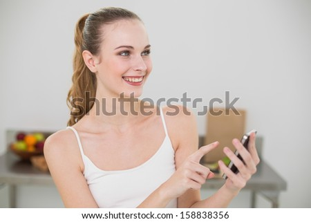Smiling young woman holding smartphone  in the kitchen at home - stock photo