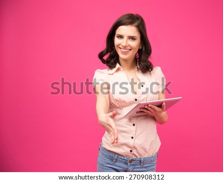 Smiling young woman holding tablet computer and stretching hand for handshake over pink background - stock photo