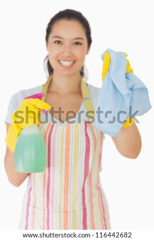 Smiling young woman holding up rag and spray bottle in apron and rubber gloves - stock photo
