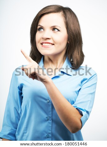Smiling young woman in a blue blouse. Indicates her finger in the upper right corner. On a gray background - stock photo