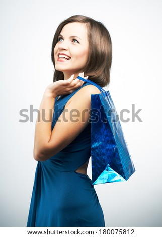 Smiling young woman in a blue dress. Holding gift bag and looking into the upper-right corner. On a gray background - stock photo