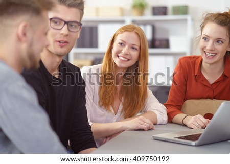 Smiling young woman in a business meeting with two male and a female colleague watching the men with an interested expression as they talk - stock photo