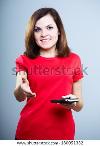 Smiling young woman in a red shirt. Keep a notepad and pen and gives hand for a handshake. On a gray background - stock photo
