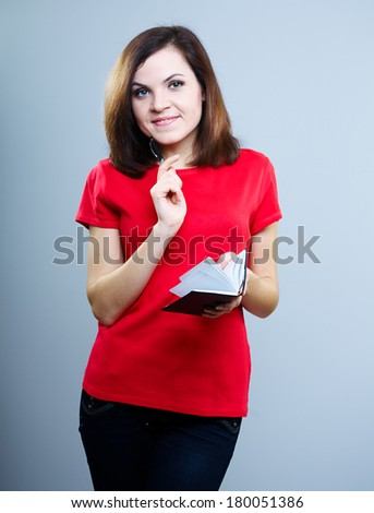 Smiling young woman in a red shirt. Keep a notepad and pen. On a gray background