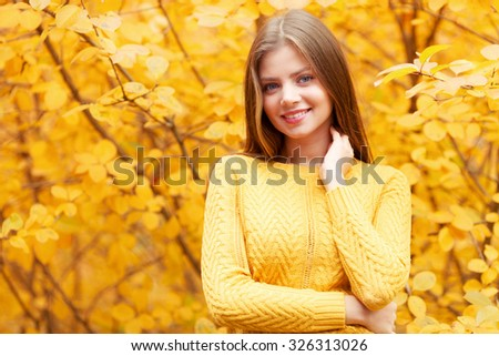Smiling young woman in autumn forest - stock photo