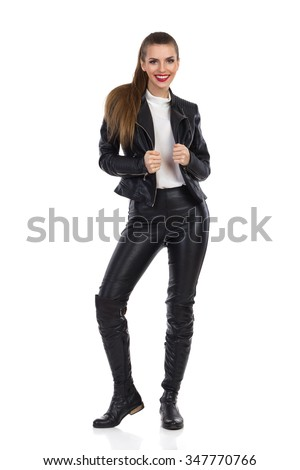 Smiling young woman in black leather trousers, jacket and boots standing and looking at camera. Full length studio shot isolated on white.