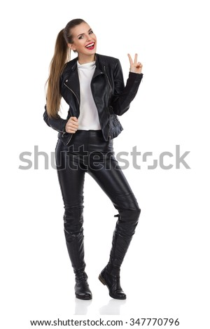 Smiling young woman in black leather trousers, jacket and boots standing, looking at camera and showing peace sign. Full length studio shot isolated on white. - stock photo