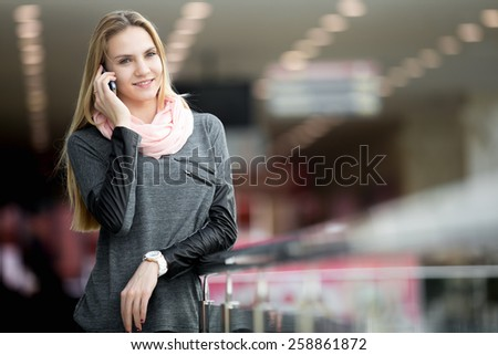 Smiling young woman in casual style clothes talking on mobile phone, making call, waiting for someone in contemporary large building, shopping center, station, copyspace - stock photo