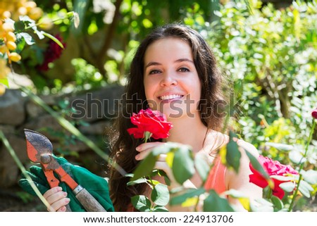 Smiling young woman in dress with pruner in yard  of home - stock photo